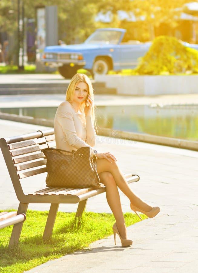 Muchacha rubia preciosa que se sienta en un banco y que habla en el teléfono La muchacha modelo mira la cámara fotos de archivo libres de regalías