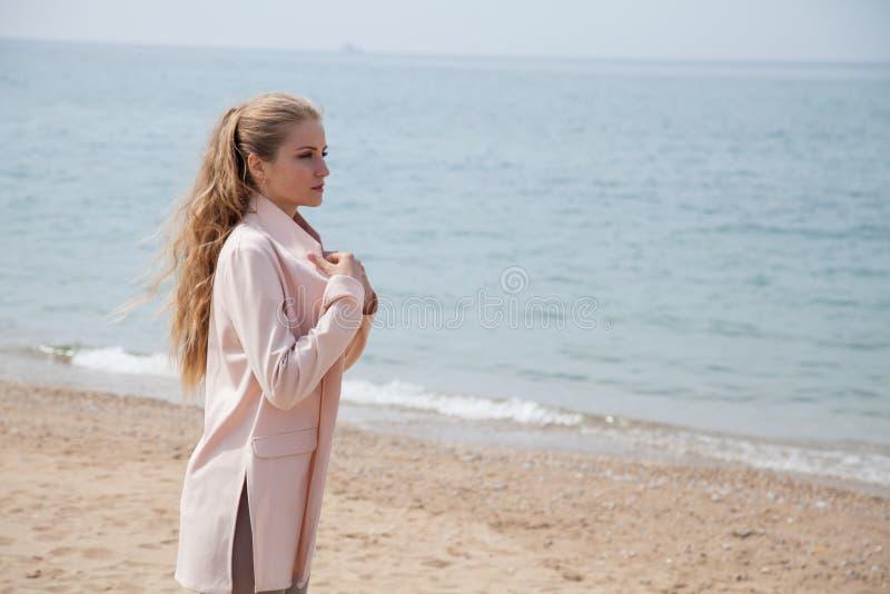 Muchacha rubia que camina en una orilla de mar de la playa arenosa foto de archivo