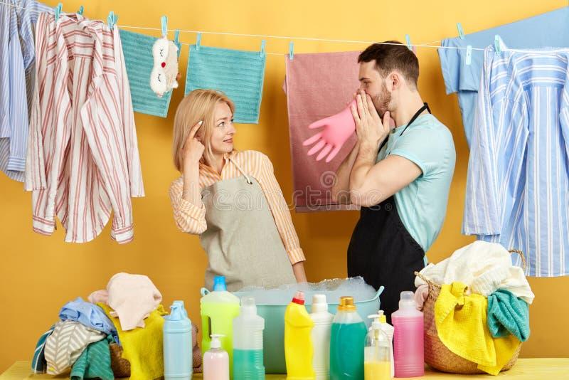 Muchacha rubia que hace un tornillo la muestra floja como su marido que infla guantes protectores del látex fotos de archivo libres de regalías