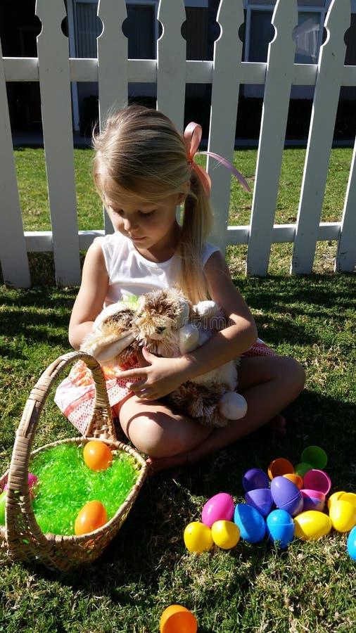 Muchacha rubia que mira los huevos de Pascua imagenes de archivo