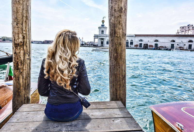 Muchacha rubia que se sienta en el embarcadero en Venecia Visión posterior fotos de archivo libres de regalías