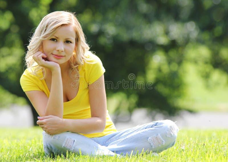 Muchacha rubia que se sienta en la hierba y la sonrisa. Mirada de la cámara. Al aire libre. Día soleado. foto de archivo
