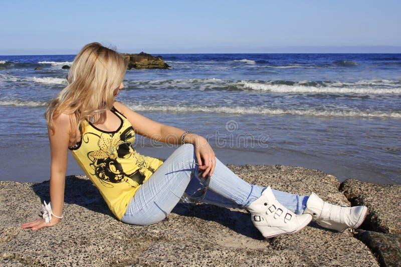 Muchacha rubia que se sienta en roca en la playa imagen de archivo