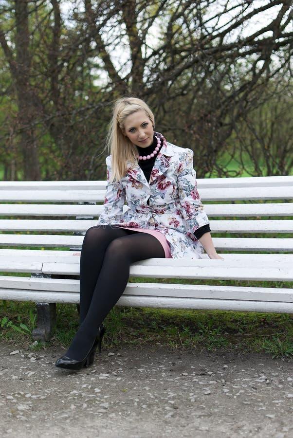 Muchacha rubia que se sienta en un banco de parque fotografía de archivo libre de regalías