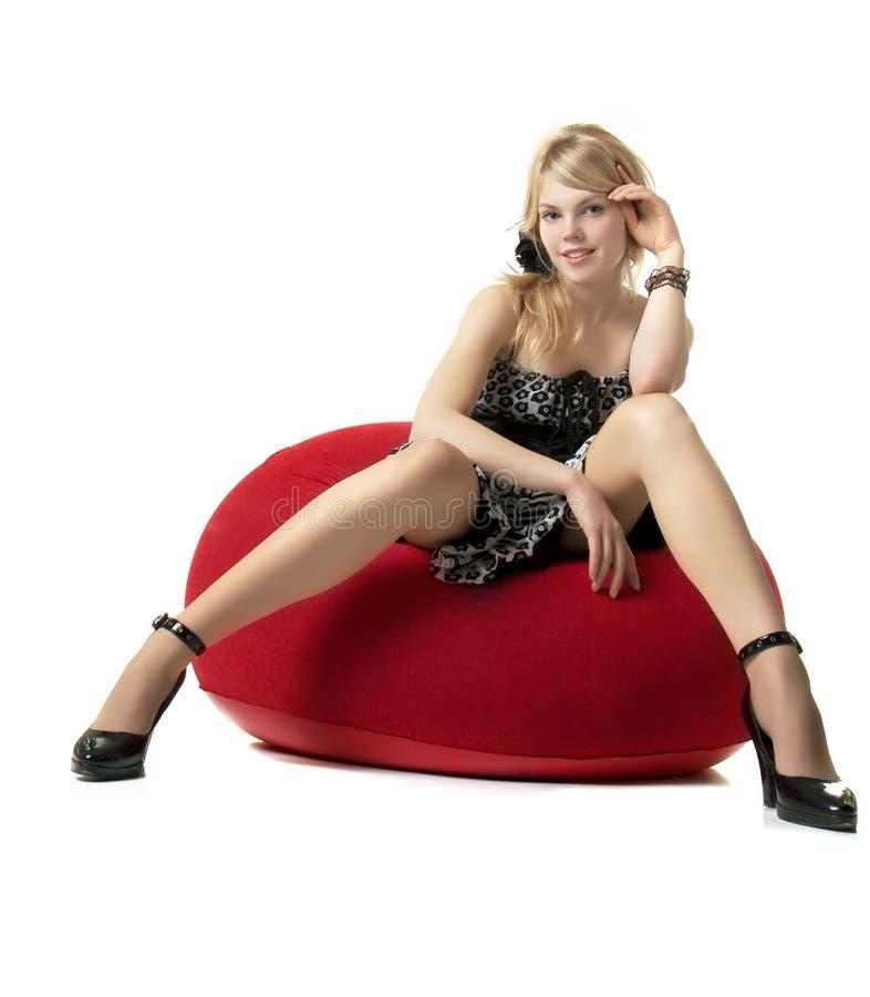 Muchacha rubia, que se sienta en una silla roja imagen de archivo