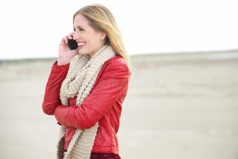 Muchacha rubia que sonríe y que habla en el teléfono celular fotografía de archivo libre de regalías