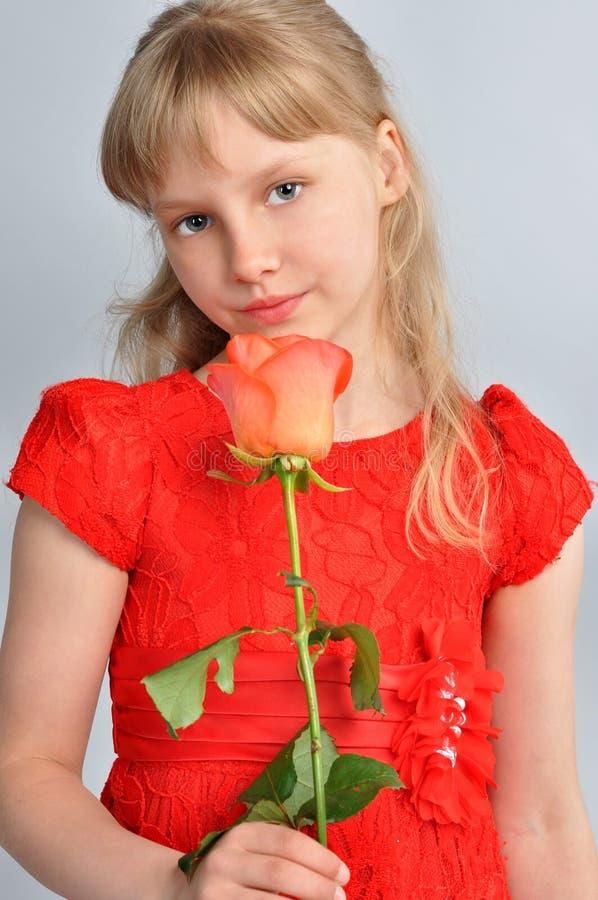 Muchacha rubia que sostiene una flor fotos de archivo