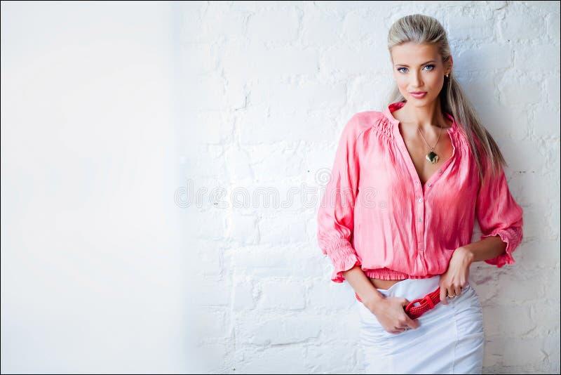 Muchacha rubia sensual atractiva hermosa en la chaqueta rosada en el Stu imágenes de archivo libres de regalías