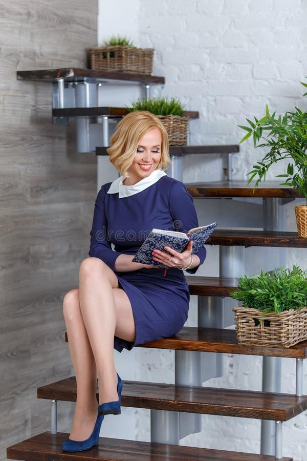 Muchacha rubia sonriente en el vestido elegante que se sienta en las escaleras con el libro imagenes de archivo