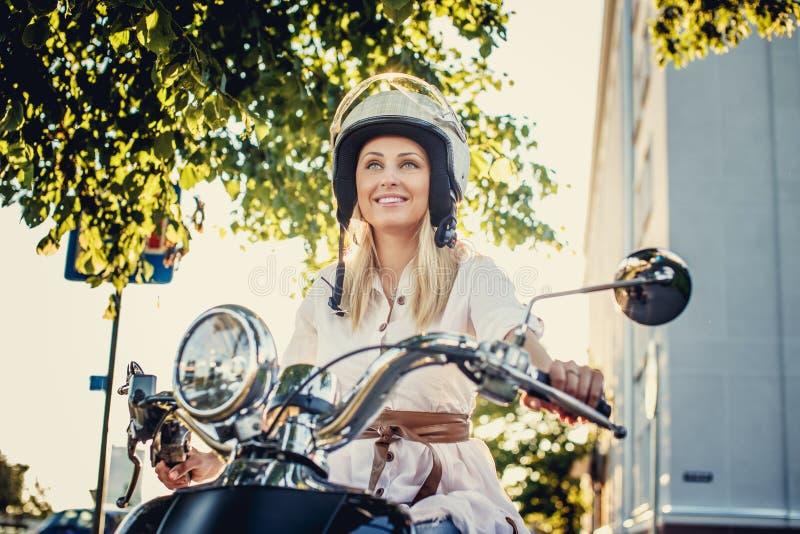 Muchacha rubia sonriente en helme del moto imagenes de archivo