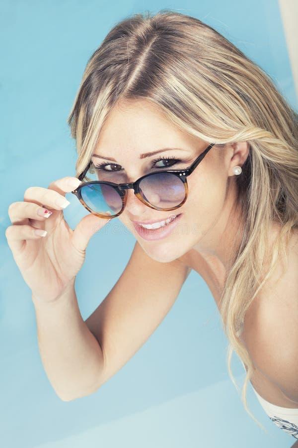 Muchacha rubia sonriente hermosa con las gafas de sol en la piscina imagen de archivo