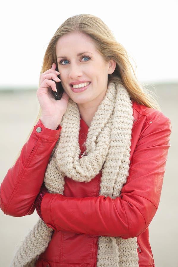 Muchacha rubia sonriente hermosa en el teléfono fotos de archivo