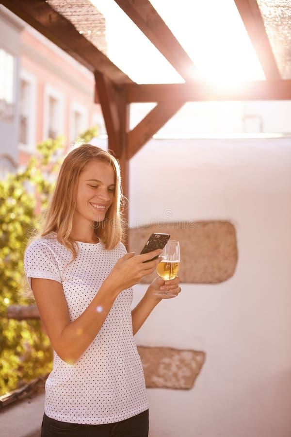 Muchacha rubia sonriente preciosa que mira el teléfono móvil imágenes de archivo libres de regalías