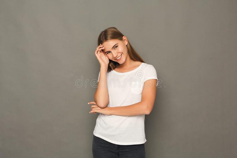 Muchacha rubia sonriente que presenta en el estudio fotografía de archivo