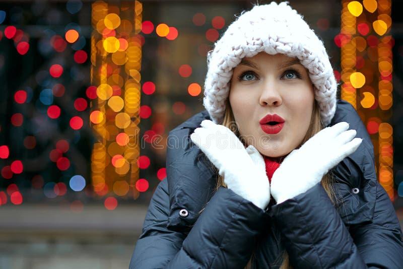 Muchacha rubia sorprendida con los labios rojos que llevan el sombrero hecho punto, presentando foto de archivo