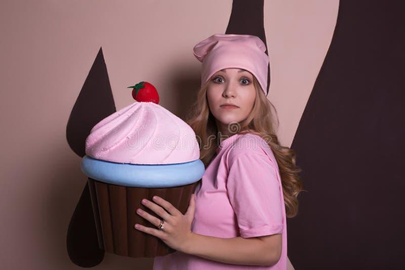 Muchacha rubia sorprendida que presenta con la decoración grande del dulce de la magdalena fotografía de archivo