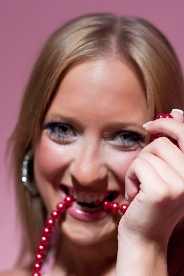 Muchacha rubia y perlas rojas imagen de archivo