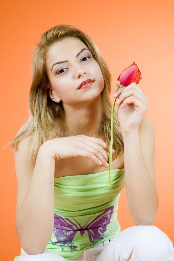 Muchacha rubia y tulipán rojo imagenes de archivo