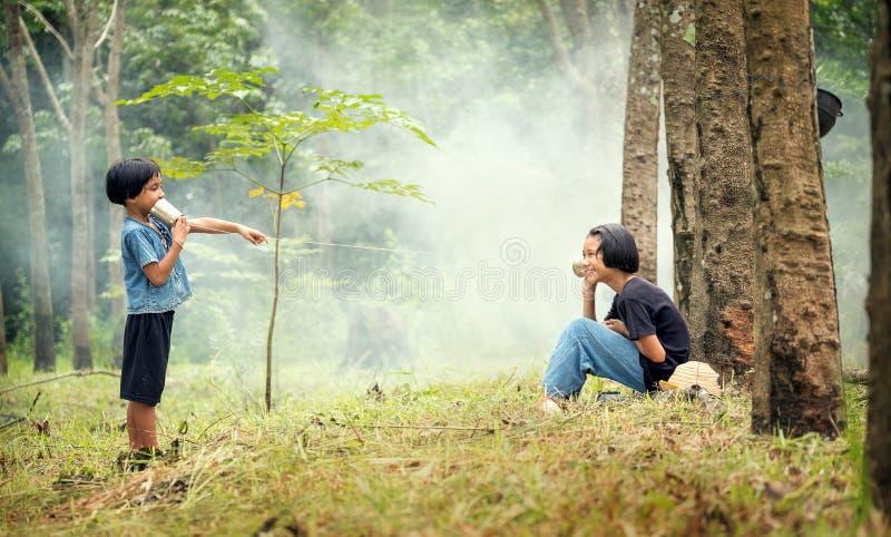 Muchacha rural asiática de los niños que habla para comunicar con el teléfono de la poder La alegr?a de la comunicaci?n entre los imagenes de archivo