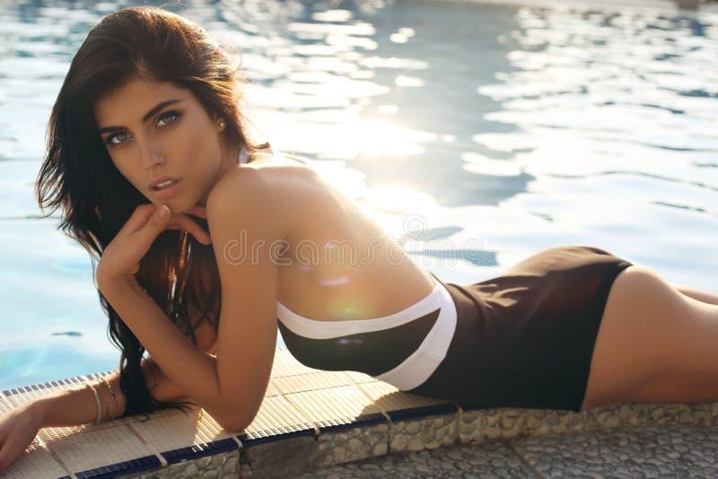 Muchacha sensual con el pelo oscuro en el traje de baño que presenta al lado de una natación imágenes de archivo libres de regalías