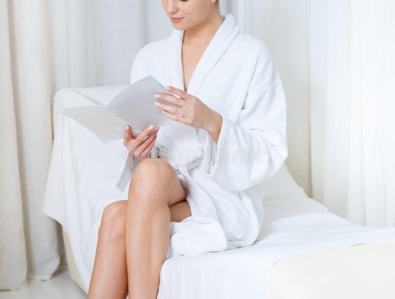Muchacha sensual que entretiene con la revista en centro de la salud fotografía de archivo libre de regalías