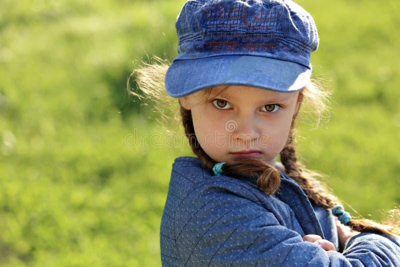 Muchacha seria enojada del niño en sombrero azul que hace muecas en gra del verde del verano imágenes de archivo libres de regalías