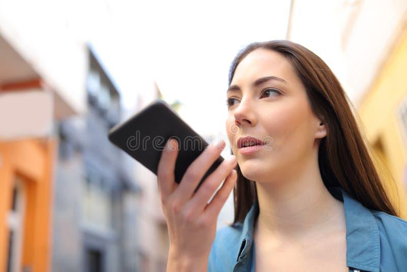 Muchacha seria que usa el app del reconocimiento vocal en el teléfono elegante foto de archivo libre de regalías
