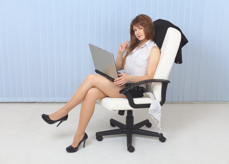 Muchacha sexual joven - la secretaria se sienta en una butaca imagen de archivo