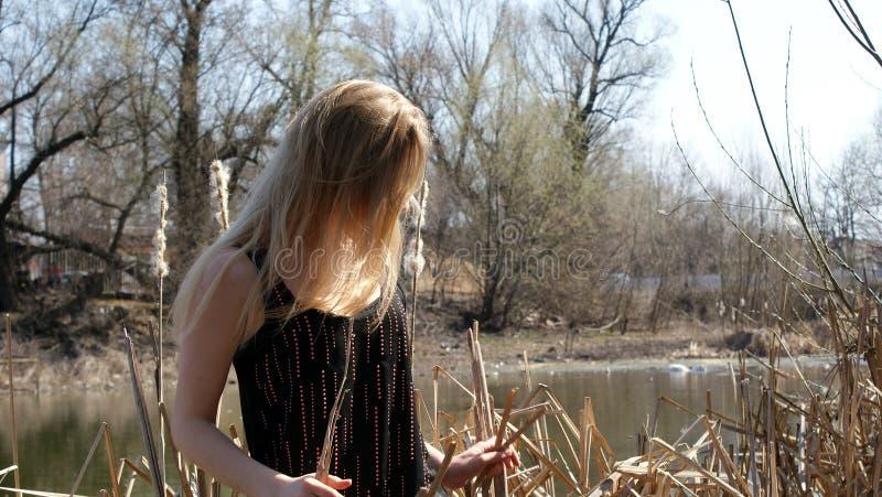 Muchacha smilling cerca del río con el vidrio imagen de archivo libre de regalías