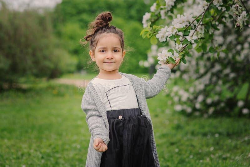 Muchacha soñadora feliz linda del niño del niño que camina en el jardín floreciente de la primavera, celebrando pascua al aire li fotos de archivo libres de regalías