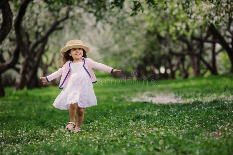 Muchacha soñadora feliz linda del niño del niño que camina en el jardín floreciente de la primavera, celebrando pascua al aire li imagen de archivo libre de regalías