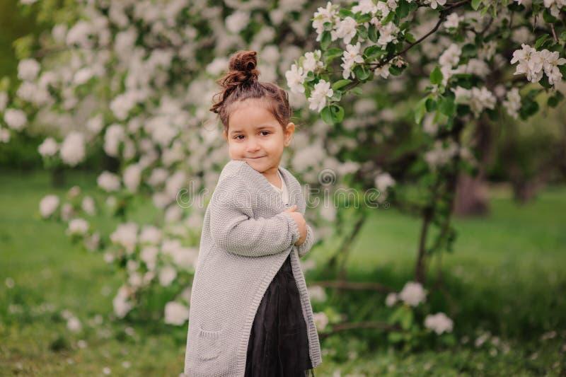 Muchacha soñadora feliz linda del niño del niño que camina en el jardín floreciente de la primavera, celebrando pascua al aire li foto de archivo