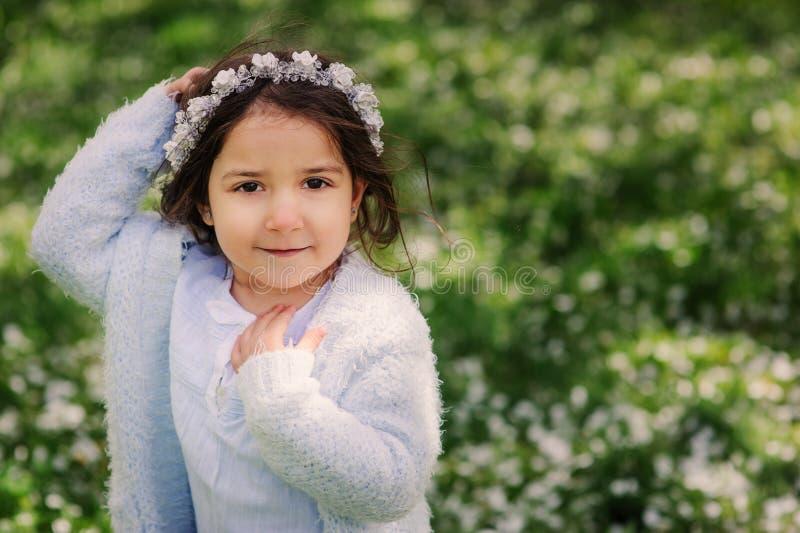 Muchacha soñadora feliz linda del niño del niño que camina en el jardín floreciente de la primavera, celebrando pascua al aire li fotos de archivo