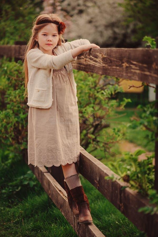 Muchacha soñadora linda del niño en el equipo beige que sube la cerca de madera rústica en jardín de la primavera imagenes de archivo