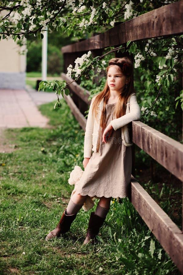 Muchacha soñadora linda del niño que presenta en la cerca de madera rústica con el oso de peluche foto de archivo