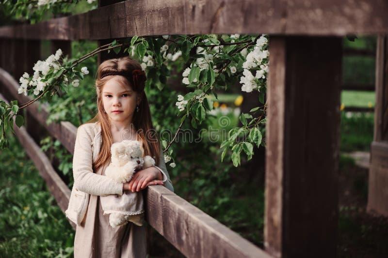 Muchacha soñadora linda del niño que presenta en la cerca de madera rústica con el oso de peluche imágenes de archivo libres de regalías