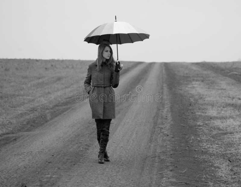 Muchacha sola con el paraguas en la carretera nacional. fotos de archivo