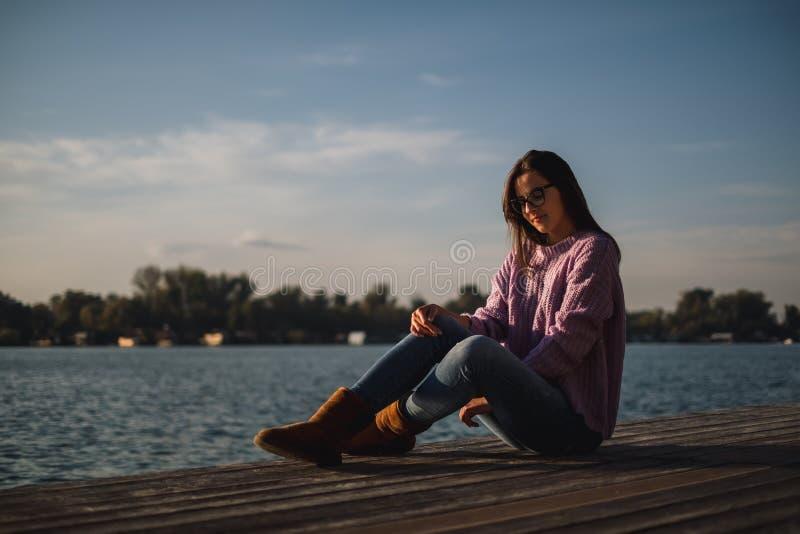 Muchacha sola con los vidrios que se sientan por el río en puesta del sol imágenes de archivo libres de regalías
