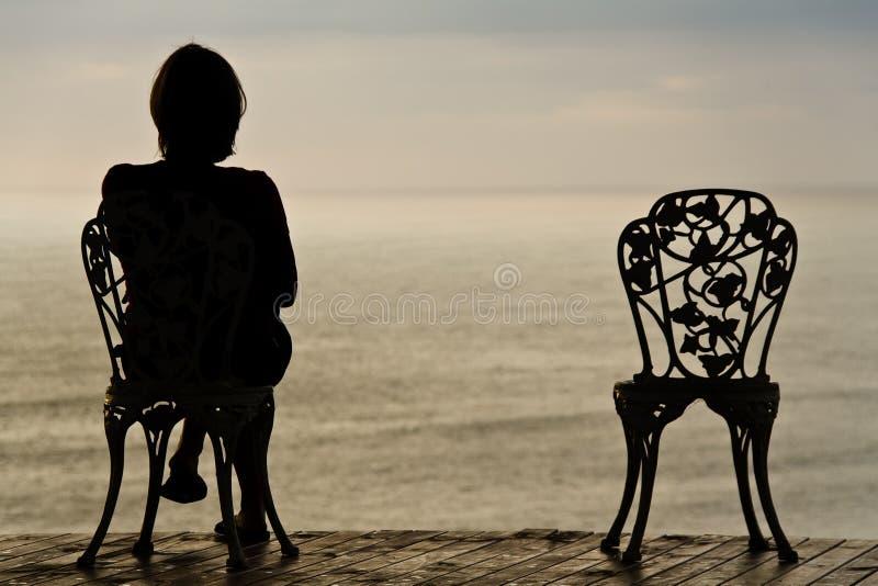 Muchacha sola en una silla foto de archivo