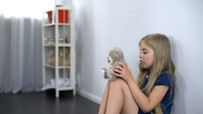Muchacha sola que juega con el juguete preferido del oso de peluche, custodia de los hijos, guardería fotos de archivo libres de regalías