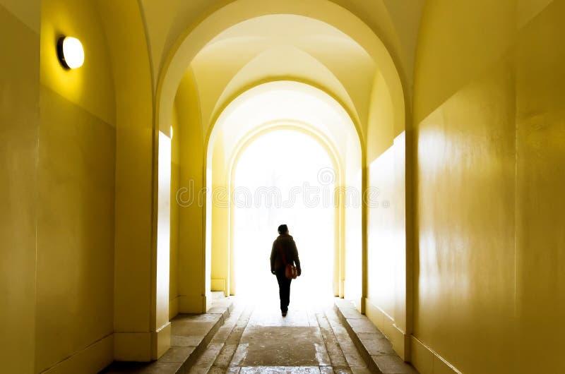 Muchacha sola que pasa adelante a través del túnel amarillo imagen de archivo
