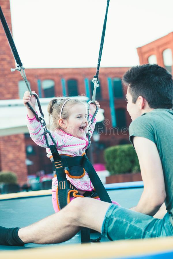 Muchacha sonriente adorable que salta en el trampolín, divirtiéndose con su hermano foto de archivo