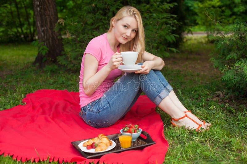 Muchacha sonriente al aire libre en el parque que tiene comida campestre foto de archivo libre de regalías