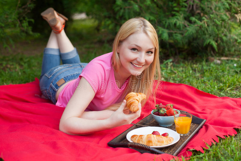 Muchacha sonriente al aire libre en el parque que tiene comida campestre imagenes de archivo