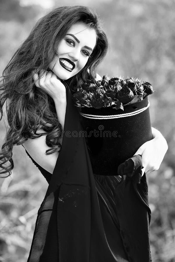 muchacha sonriente atractiva con las rosas rojas fotografía de archivo