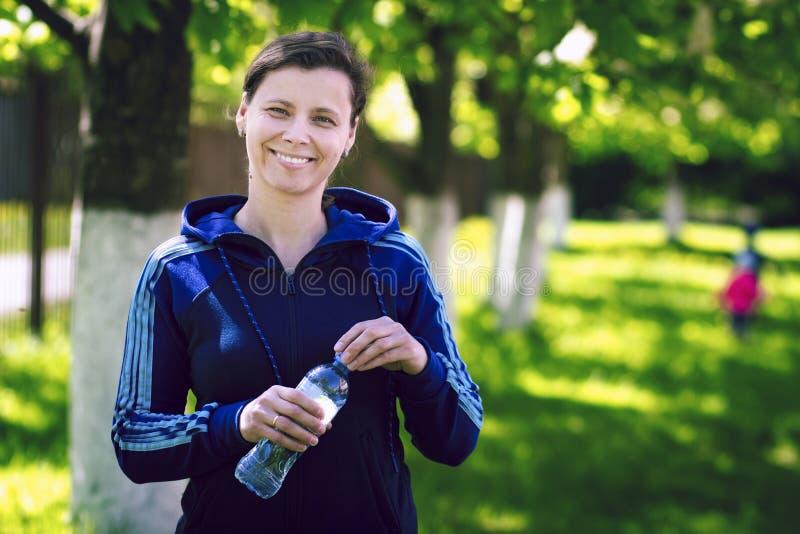 Muchacha sonriente atractiva joven en camiseta de los deportes con la botella de agua en su mano en parque verde del verano foto de archivo
