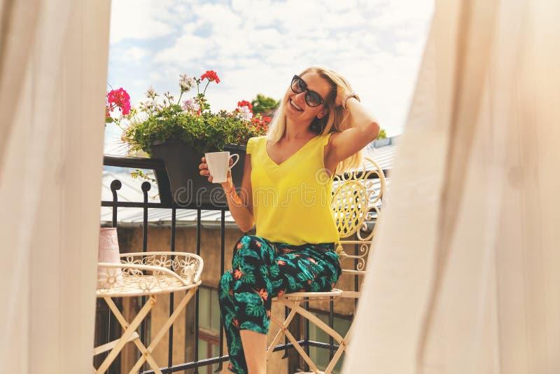 Muchacha sonriente atractiva que se relaja en balcón y que come café del desayuno foto de archivo