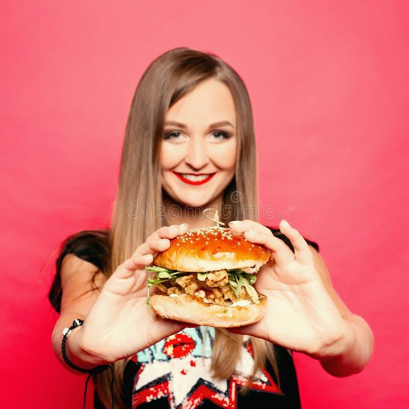 Muchacha sonriente bonita con la hamburguesa en manos en primero plano foto de archivo libre de regalías