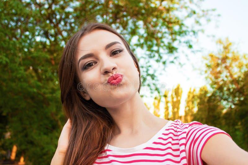 Muchacha sonriente bonita que hace el selfie, morenita de pelo largo en la ropa blanca, primer fotografía de archivo libre de regalías