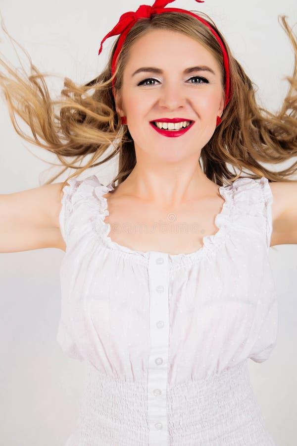 Muchacha sonriente caucásica atractiva del perno-para arriba con el pelo que sopla En blanco foto de archivo libre de regalías